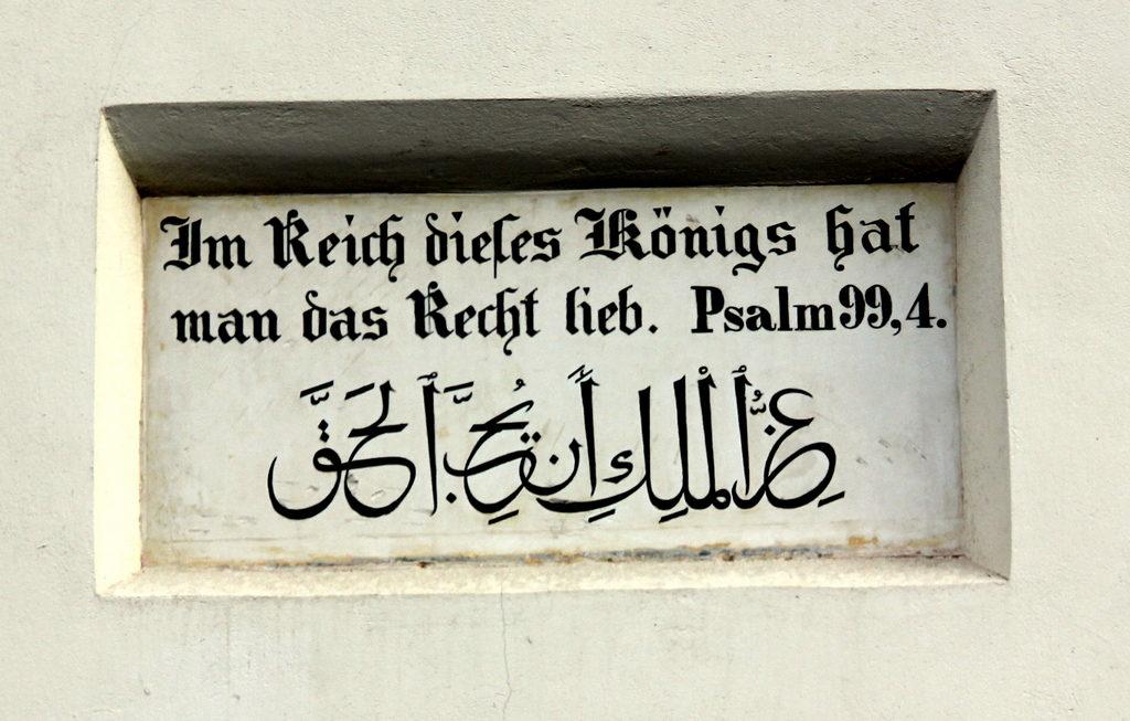 آية من مزمور 99 من «العهد القديم» باللغة العربية والألمانية فوق بوابة أحد بيوت سارونا