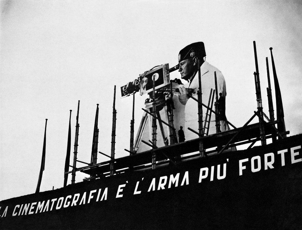 لوحة إعلانية تحمل وجه موسوليني مع كاميرا سينمائية مع جملة (السينما هي السلاح الأقوي) - إيطاليا 1937